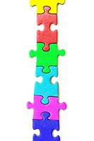 Multi-coloured pieces of a jigsaw in a line