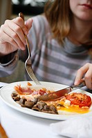 Teenager eating an english breakfast