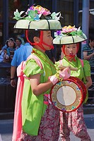 A young participant wearing a flower hat and carrying a drum
