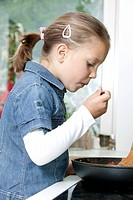 portrait of young girl cooking in kitchen
