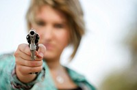 Woman in fear pointing gun