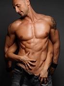 Woman´s hands touching young muscular man´s body
