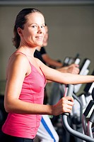 People exercising on elliptical trainer in gym