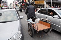 Shanghai (China): a man trying to proceed with his bicycle-cart trough the traffic madness at the Yuyuan Bazaar