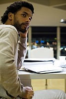 Man sitting at desk in office at night, looking away in thought