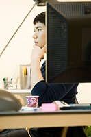 Young man sitting at desk, looking away in thought
