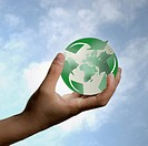 Hand holding planet earth enveloped by recycling symbol