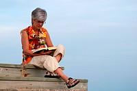 Frau sitzt auf Holztreppe und liest ein Buch