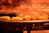 Schwenkgrill mit Brötchen und Bratwürsten, hanging grill with roast sausages and rolls