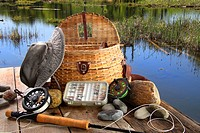 Traditional fly_fishing rod with equipment beside a lake