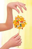 Pills from an orange lollipop