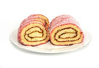 Jelly roll cut in half on plate against white background