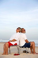 Mature couple sitting back to back at beach, Praia de Manta Rota, Algarve, Portugal