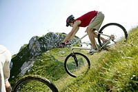 Two young men on mountainbikes driving downhill over a meadow part of