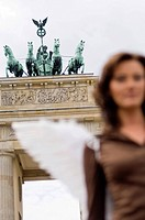 Woman with angel wings in front of Brandenburg Gate, Berlin, Germany