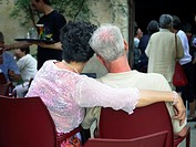 A man and woman sitting in a cafe show affection for each other