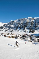 Austria, Vorarlberg, Lech am Arlberg, Group of skiers skiing on ski piste near village in winter