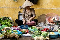 Woman selling fruits and vegetables on the street market in old Hanoi city.
