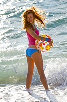 Attractive young woman with an inflatable ball on the beach