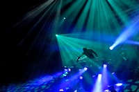 DJ engulfed in lights at a dance club, disco or rave