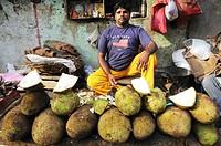 Man at the market selling Jack fruits, New Delhi, India