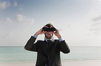 Businessman using binoculars on beach
