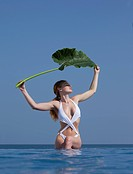 Woman holding leaf in infinity pool