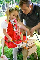 Girl age 5 dressed for Midsommar at the Swedish Institute with her father at a work bench  Minneapolis Minnesota MN USA