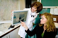Dentist helping a patient understand a dental treatment using the computer  St Paul Minnesota MN USA