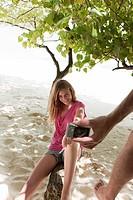 Man taking photo of girlfriend in tree