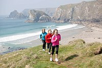 Family running on cliffs over beach