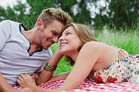 Couple laying on picnic blanket