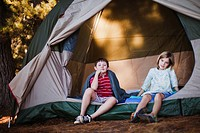 Children sitting in tent at campsite