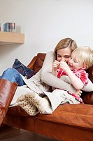 Mother and son hugging on sofa