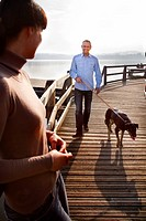 Couple walking dog on pier