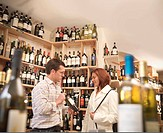 Wine merchant with customer in shop