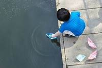 Boy playing with paper sailboats in pond