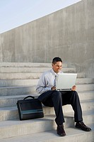 Businessman using laptop on steps
