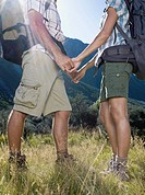 Hikers holding hands in grass