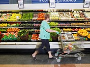 Woman examining produce in grocery store