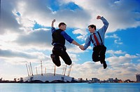 Businessmen jumping against city skyline
