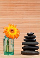 Orange snflower in a glass flask beside a black stones stack against a bamboo background
