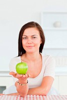 Young woman showing an apple with the camera focus on the fruit