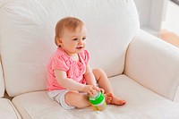 Blond baby playing with a ball while sitting on a sofa in the living room