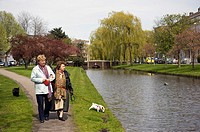 Rotterdam, Netherlands. An elderly mother and her adult daughter walking their pet dog, along side a Rotterdam canal.