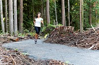 Young Woman Jogging on Trail Through Recently Cut Forest, Redmond, Washington, USA