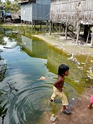 CAMBODIA. Girl playing in polluted pond  Don Tok village, Kampot, lies beside a river estuary and is often flooded by sea water, a consequence of clim...