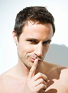 Portrait of a bare chested man with finger on lips