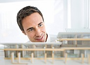 Business man looking at architectural model