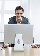 Young business man in front of computer, smiling